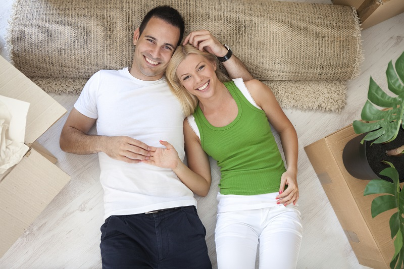 Smiling young couple lying on floor of new flat