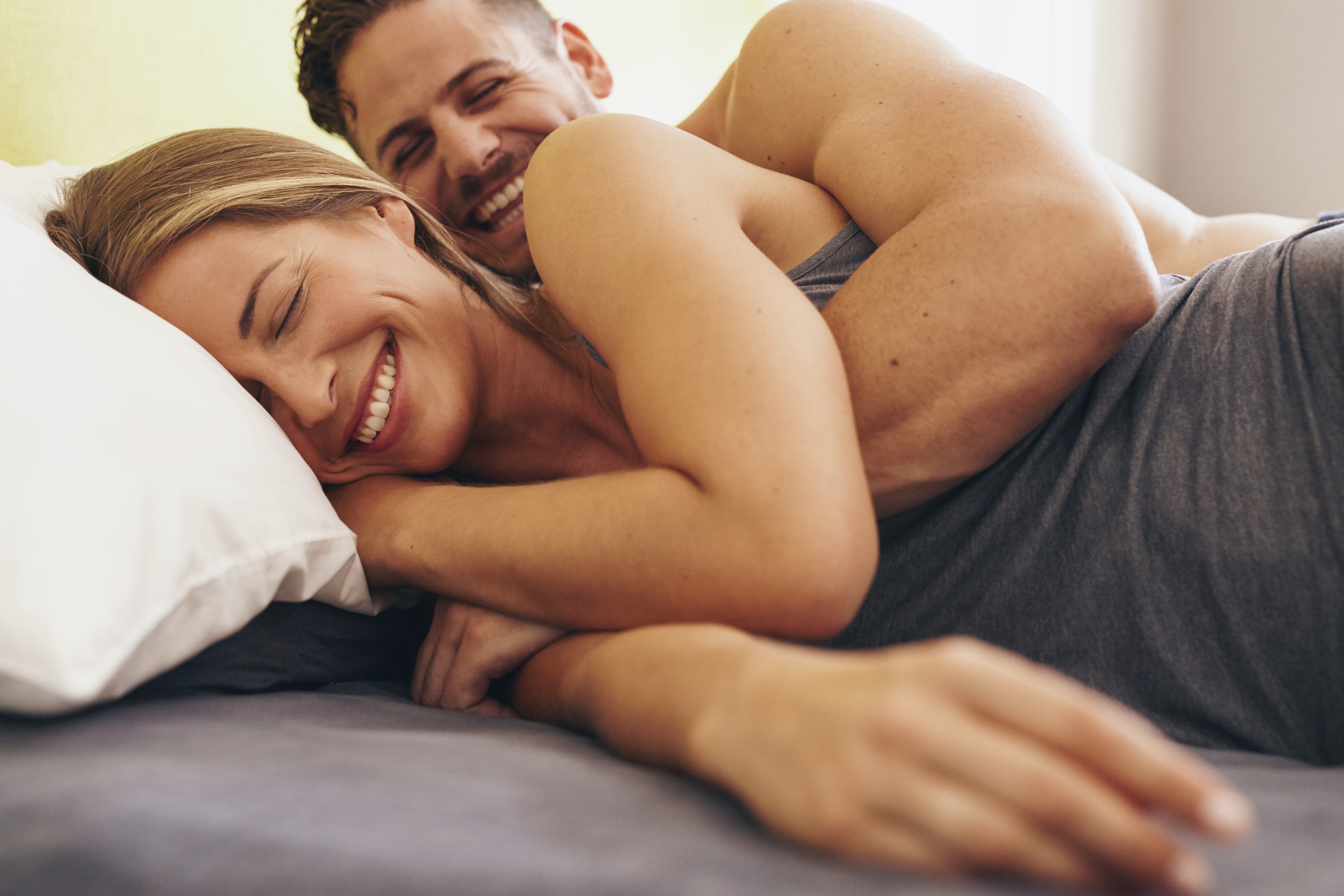 Image of cute young couple in love lying on bed. Man waking up his wife in morning.